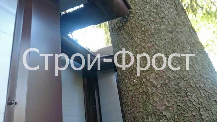 Гараж из сэндвич-панелей построен вплотную к дереву