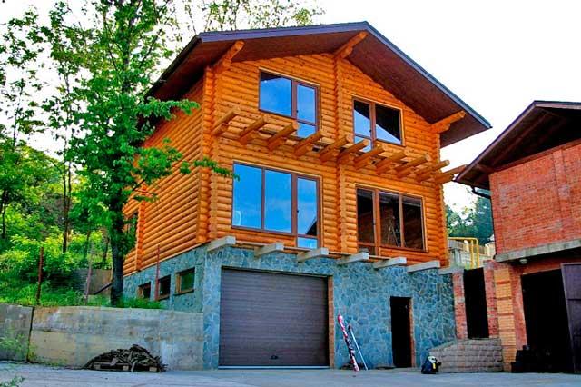 На участке с уклоном можно построить дом из бревна с гаражом в цоколе. Это удобный и практичный вариант, занимающий минимальную площадь.