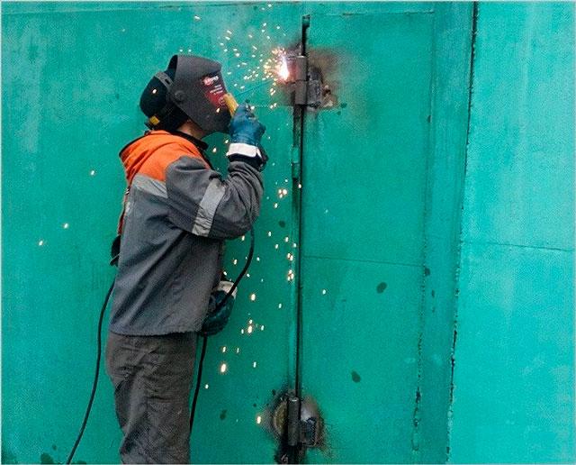 Сварщик приваривает новые петли к металлическим воротам - согласитесь, привычная картина